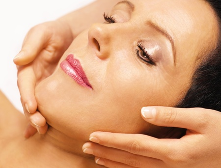 Young woman lying on her back, gets massage,reiki,on her face ,  Stock Photo