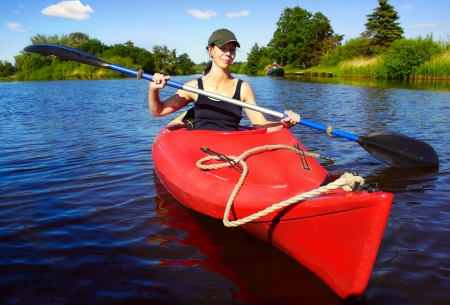 canoe paddle: Girl with paddle and kayak on a small river in rural landscape