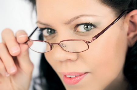 brainy: Smart young woman face overlooking her eyeglasses,close-up