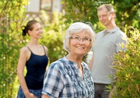 Senior woman smiling in front of two young people, outdoors Stock Photo - 14446851