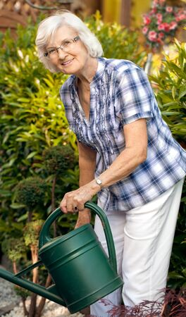 Senior woman watering her garden with watering can photo