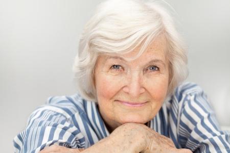 arrugas: Retrato de mujer mayor, sobre fondo gris con el pelo blanco Foto de archivo