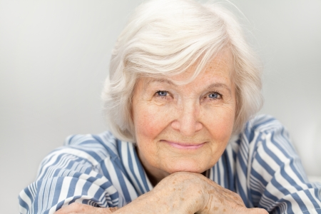 gracious: Senior woman portrait, on  grey  background with white hair  Stock Photo