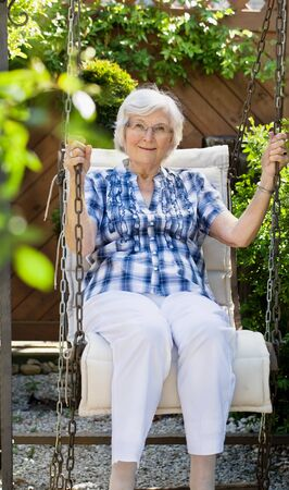 gracious: Senior woman  swinging on a garden-swing in summer Stock Photo