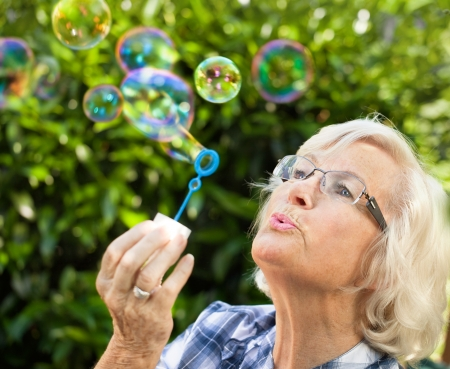 woman blowing: Senior woman is blowing bubbles in the garden,close-up