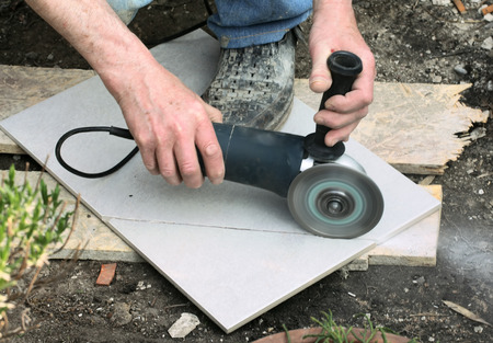 Craftsman Is Cutting A Floor Tile With A Portable Angle Grinder