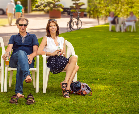 people sitting on chair: Two people sitting on a chair in the park in summer, drinking beer and water