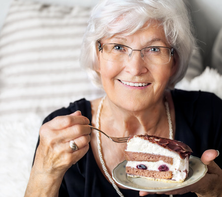 Senior lady looking happy at camera, she likes to eat a piece of creamcake