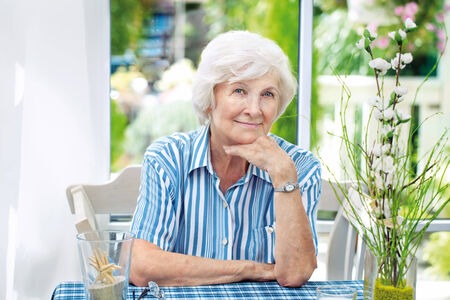sunroom:  Beautiful senior woman sitting in her winter garden , in the background the garden