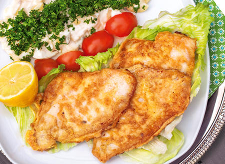 Baked plaice filet with potato salad on a plate with tomato and salad decoration Stock Photo