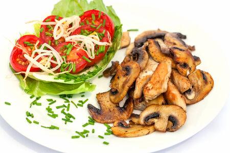turkey hen: Placa con ensalada de tomate frito gallina y pavo tiras con setas de bot�n en el fondo blanco