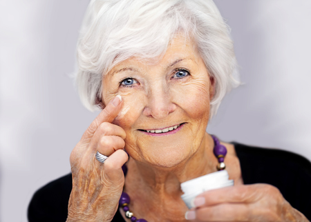Happy senior woman applying creme on her face Stock Photo