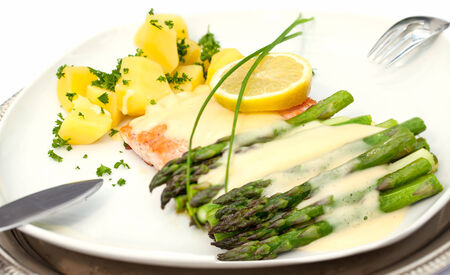 epicure: Baked salmon with asparagus, lemon, potatoes and sauce hollandaise on a plate