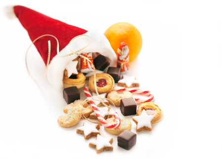 'saint nicholas': Cap of saint nicholas filled with sweets and chocolate on white background