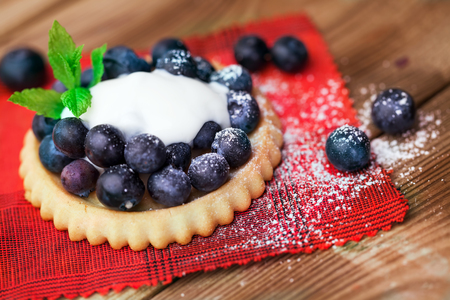 Blueberry on a biscuit with cream on wooden background