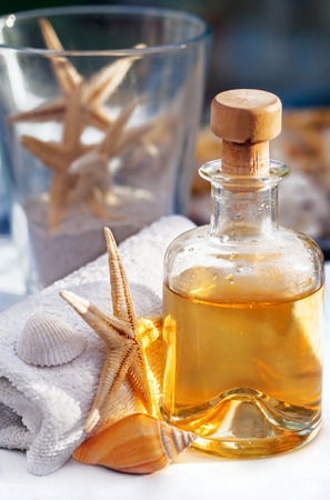 Bottle with oil for massage, aromatherapy and a towel, starfish and snail decoration