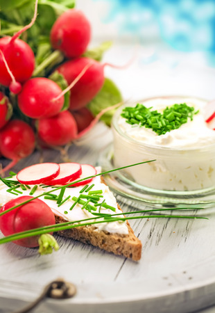 vigorously: A bowl with curd and radish and a heart shaped chives decoration and brown bread