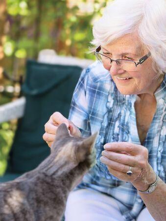Senior woman having fun with a cat in the garden