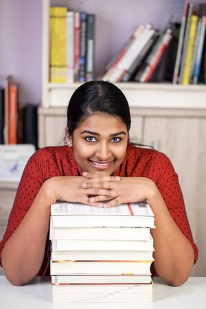 Young pretty india woman sitting at a table, hands on a staple of books, lokking happy at camera, vertical Stock Photo
