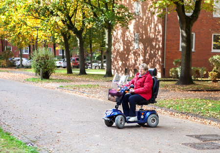 assistive: Senior woman driving with her scooter on the street