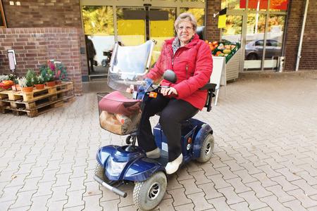 Senior femme conduite avec son scooter au supermarché Banque d'images