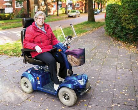 persona mayor: Mujer mayor que conduce con su vespa