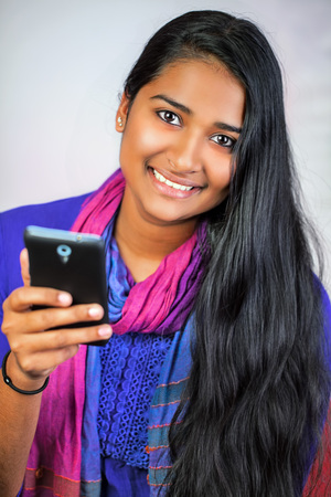 Young pretty india woman looking and smiling, holding her smartphone, vertical