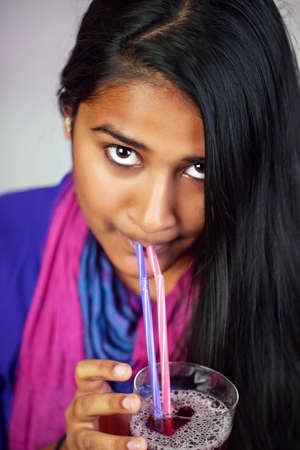 Indian MÃ??,¤dchen drinking high looking with straws from a juice glass.