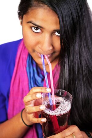 Indian woman looking up, drinking straws with a glass of juice, focus on hands Stock Photo