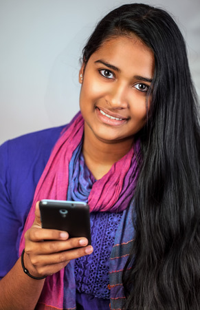Young pretty india woman looking and smiling at camera with her smartphone, vertical Stock Photo