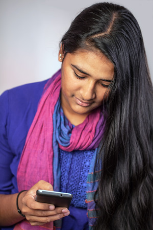 Young pretty india woman looking at her smartphone, vertical Stock Photo