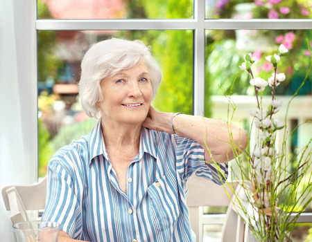 sunroom: Beautiful senior woman sitting in her winter garden, one hand on her neck, in the background the garden