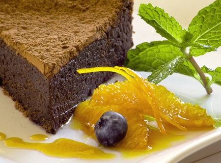 chocolate cake with orange garnish and mint photo