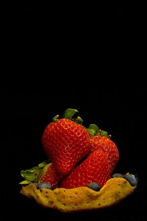 strawberries in ginger bread snap cookie basket on dark background Stock Photo