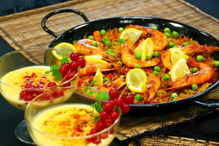 crema: Crema catalana with red fruits and sea-food paella lunch on a menu presentation  Both are very popular dishes in the Spanish cuisine  Stock Photo