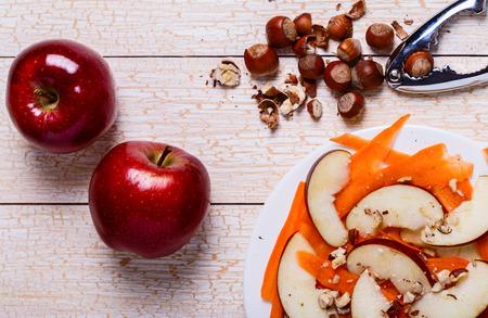manzana roja: Ensalada fresca con las manzanas, las zanahorias, las avellanas en un fondo de madera blanca Foto de archivo