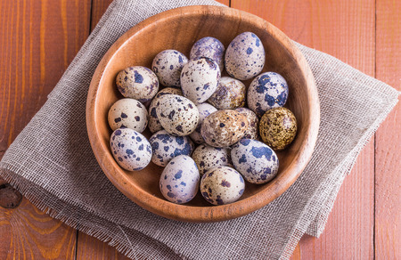 upper class: Quail eggs in a wooden bowl on a wooden table