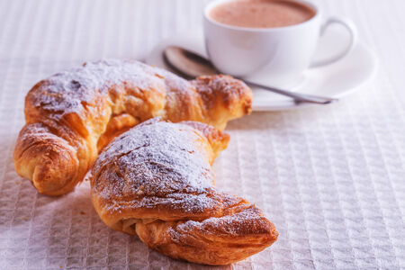 gold flax: croissants with hot chocolate on a white linen tablecloth