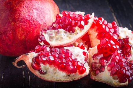 a pomegranate: juicy pomegranate and pomegranate parts on a black background Stock Photo
