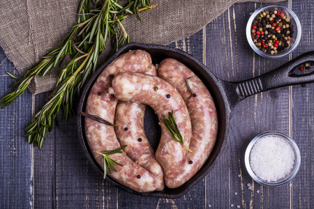 Raw sausage with spices on a dark wooden background