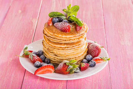 slew: Homemade pancakes with berries and fruit on a pink background Stock Photo