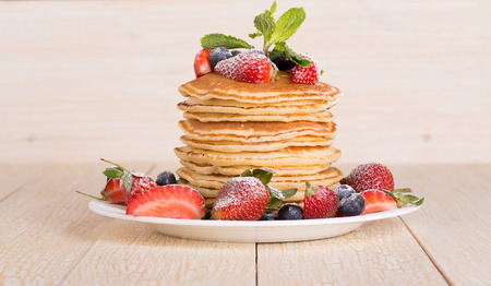slew: Homemade pancakes with berries and fruit on a white background