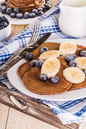 slew: Homemade chocolate pancakes with berries and banana on white background
