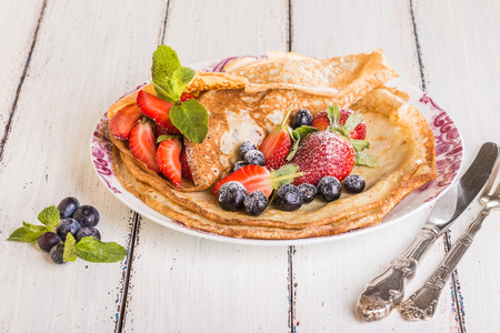 slew: Homemade crepes with berries and fruit on a white background
