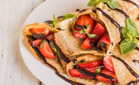 slew: Homemade Crepes with strawberries and chocolate syrup on a white background Stock Photo