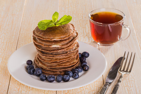 slew: Homemade chocolate pancakes with berries on white background
