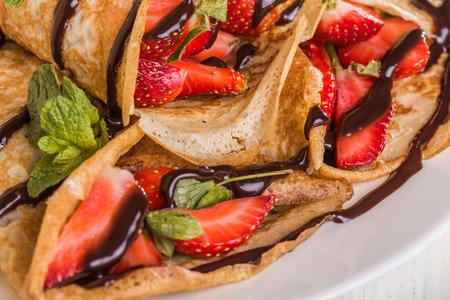 chocolate syrup: Crepes hechas en casa con las fresas y el jarabe de chocolate sobre un fondo blanco Foto de archivo