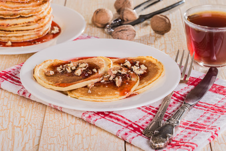 slew: Homemade pancakes with walnuts and strawberry jam on a white background