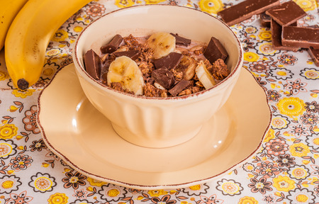 chocolate cereal: Chocolate cereal with milk, banana and chocolate chips on a colorful textile background