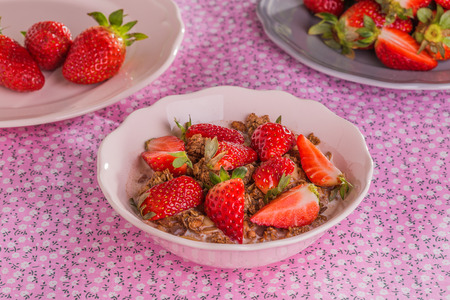 chocolate cereal: Chocolate cereal with milk and strawberries on pink textile background.